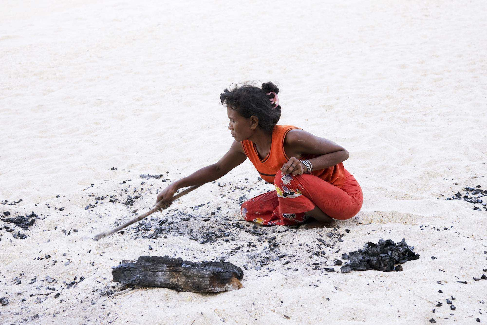 34.Sabai collecting the charcoal when the heat has calmed.jpeg