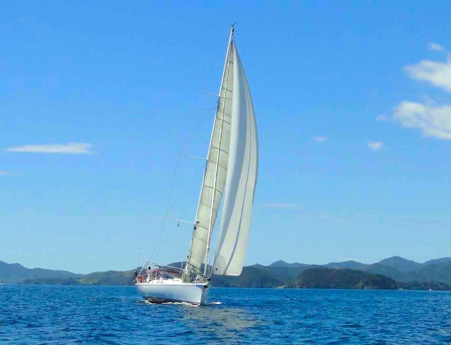 Dalai_white boat under full sail on rippled waters in Mergui Islands_XS.jpeg