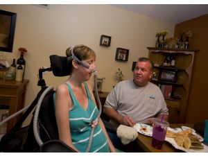 Mark Patterson tends to his wife Kelley who suffers from ALS or Lou Gehrig's disease. The family recently was able to get help from a caregiver twice a week paid for by Trish's Angels of Laguna Niguel.  PHOTO CREDIT: ROSE PALMISANO, ORANGE COUNTY REGISTER