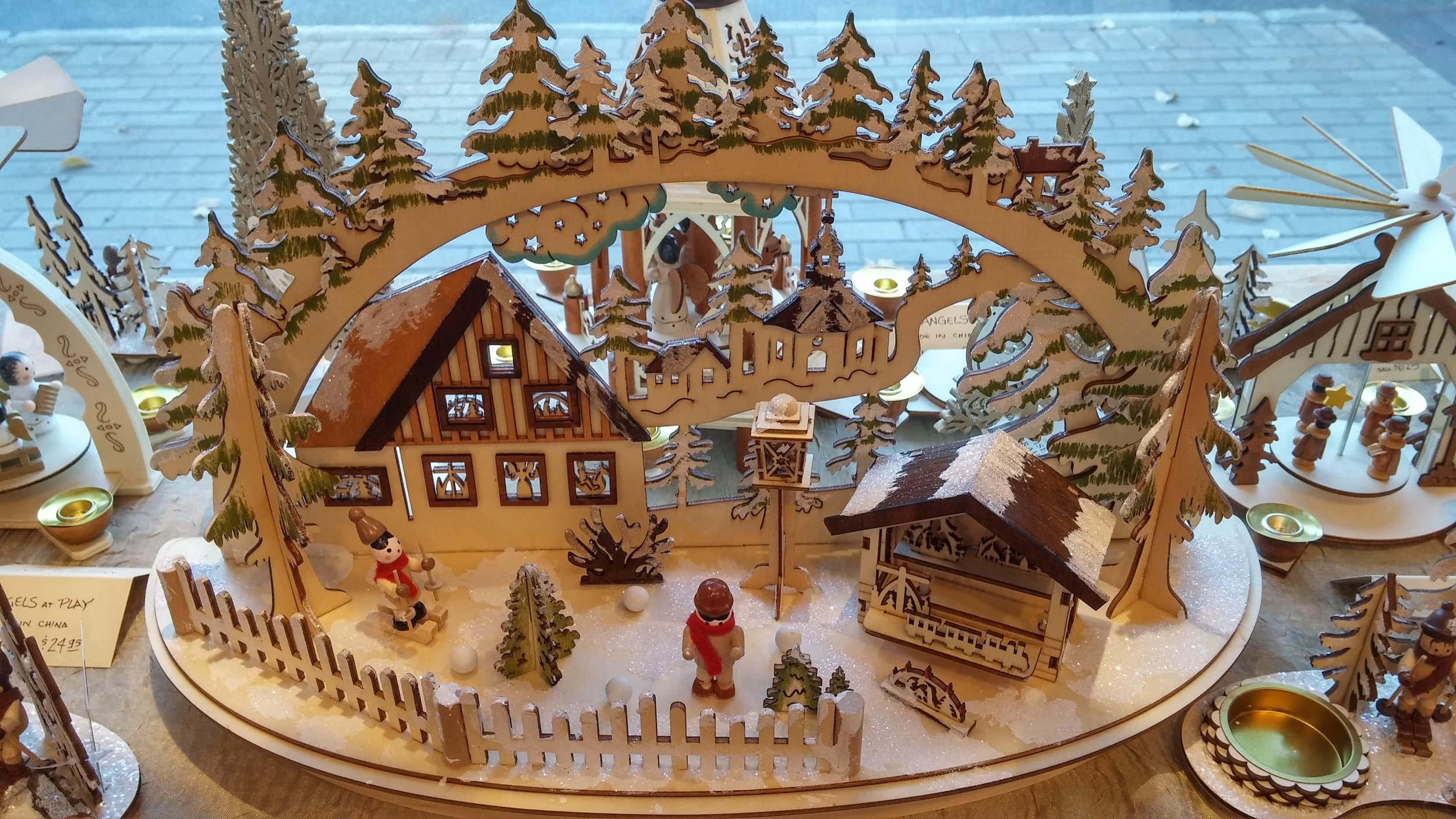 A glittery wonderland in miniature is depicted in this detailed wooden scene. The house, with the church in the distance, the trees rising up on the hillside beyond, the tiny skier and scarf wrapped gent behind a white picket fence... this magical vignette is perfect for your console or mantle.  November 9, 2017