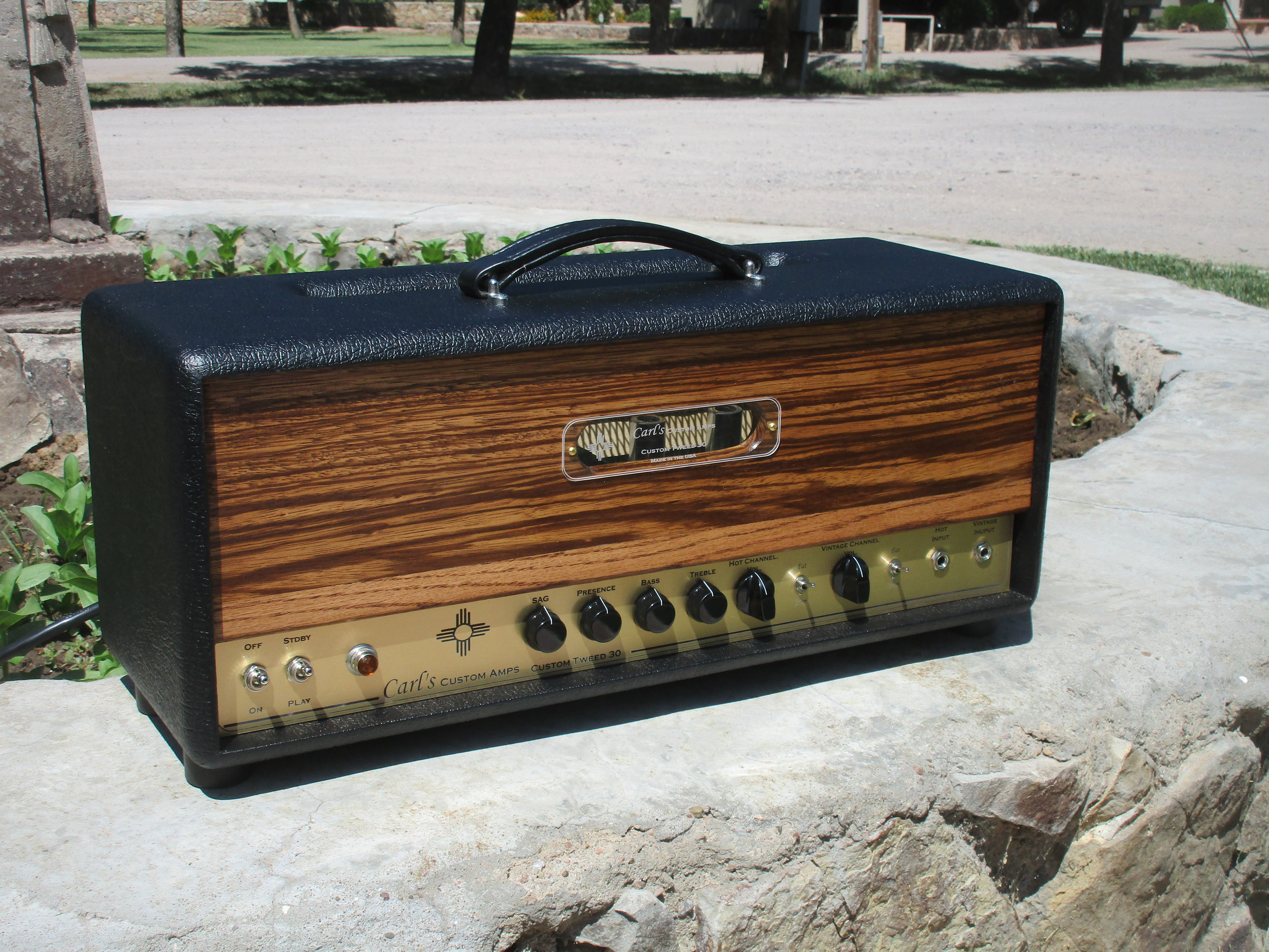 This is one my new favorite custom builds. I'm pretty thrilled with how the front came out. It got a unique tweed type circuit that can be nice and clean or really overdriven and gritty. It's 30W with NOS 6V6s for big creamy tone. There are Hot and Vintage channels and the mini-switches help adapt the amp to different guitars. A SAG control give you everything from a solid-state rectifier feel to a tube rectifier and beyond. The front is oak and zebra wood and just for kicks the logo lights up! The customer loves it….