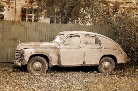 Oude auto tegen schutting aan.jpg
