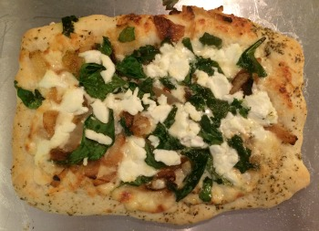 Saturday Lunch pizza--his dough, his stretching method. It looks more pale in this picture than it was. I always brush olive oil with herbs and garlic on the crust right before and immediately following baking, so that's what you're seeing on the crust. This version: Parmesan cream sauce, caramelized onions, spinach, and goat cheese. Yum!