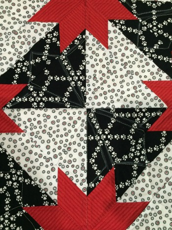 Quilted--you can see the chalk lines and stitching on the black but the thread blends on the white and red.