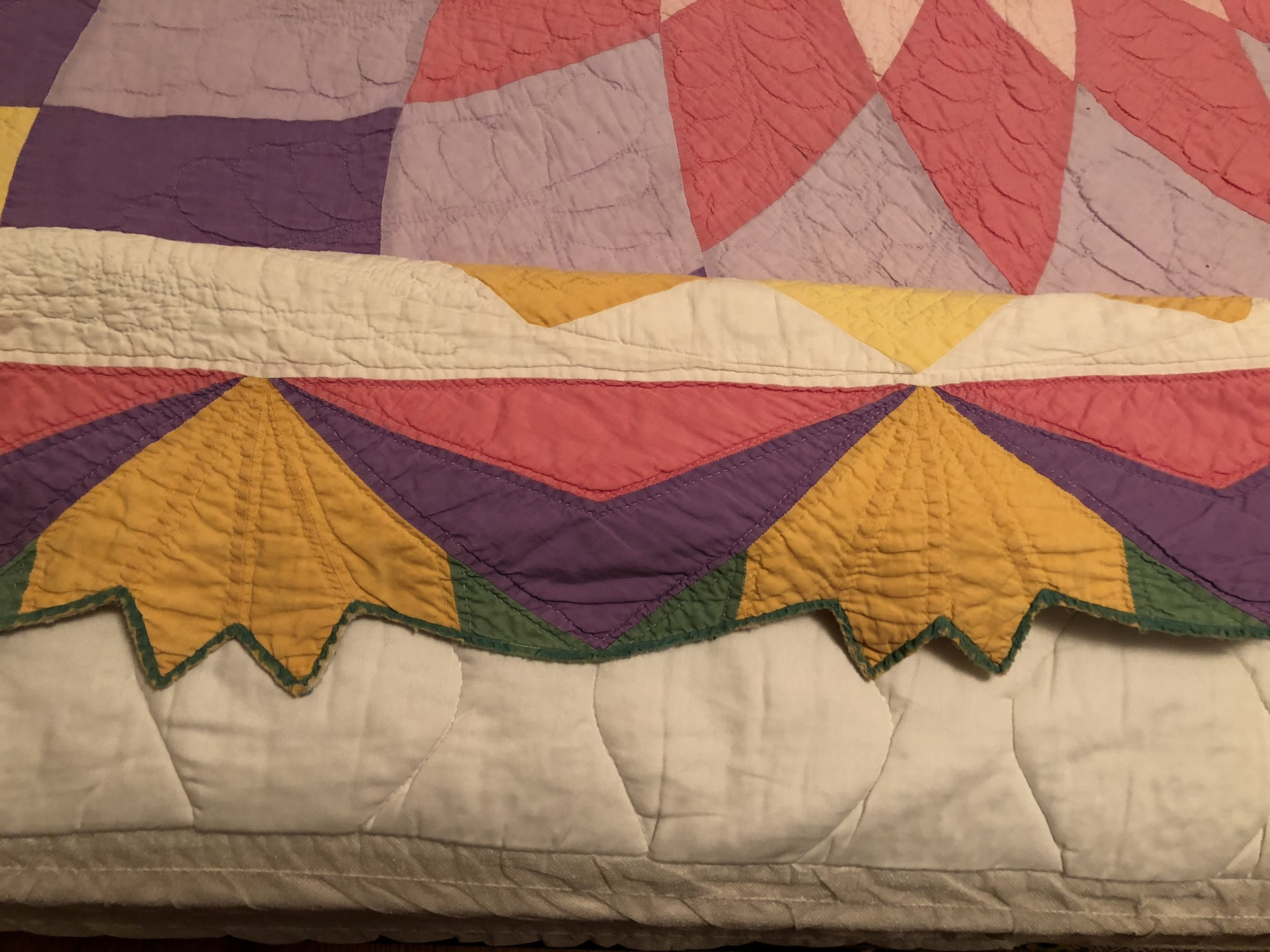 Here's the border close-up. I pulled a part of it up onto the bed to show it better. The room was small so I couldn't get a good shot of the whole border. The binding has frayed significantly—I told her she could have that repaired if she wanted to but I actually sort of like it with the original. Shows it's well-loved.