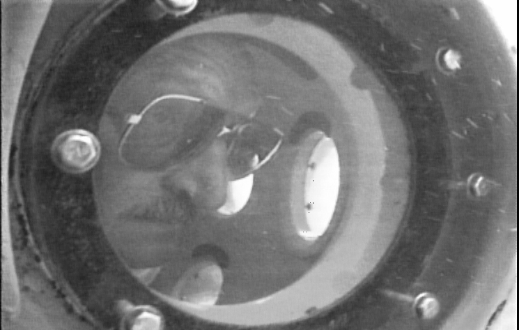 Frank Mays peers out of the porthole of the submersible delta 1995