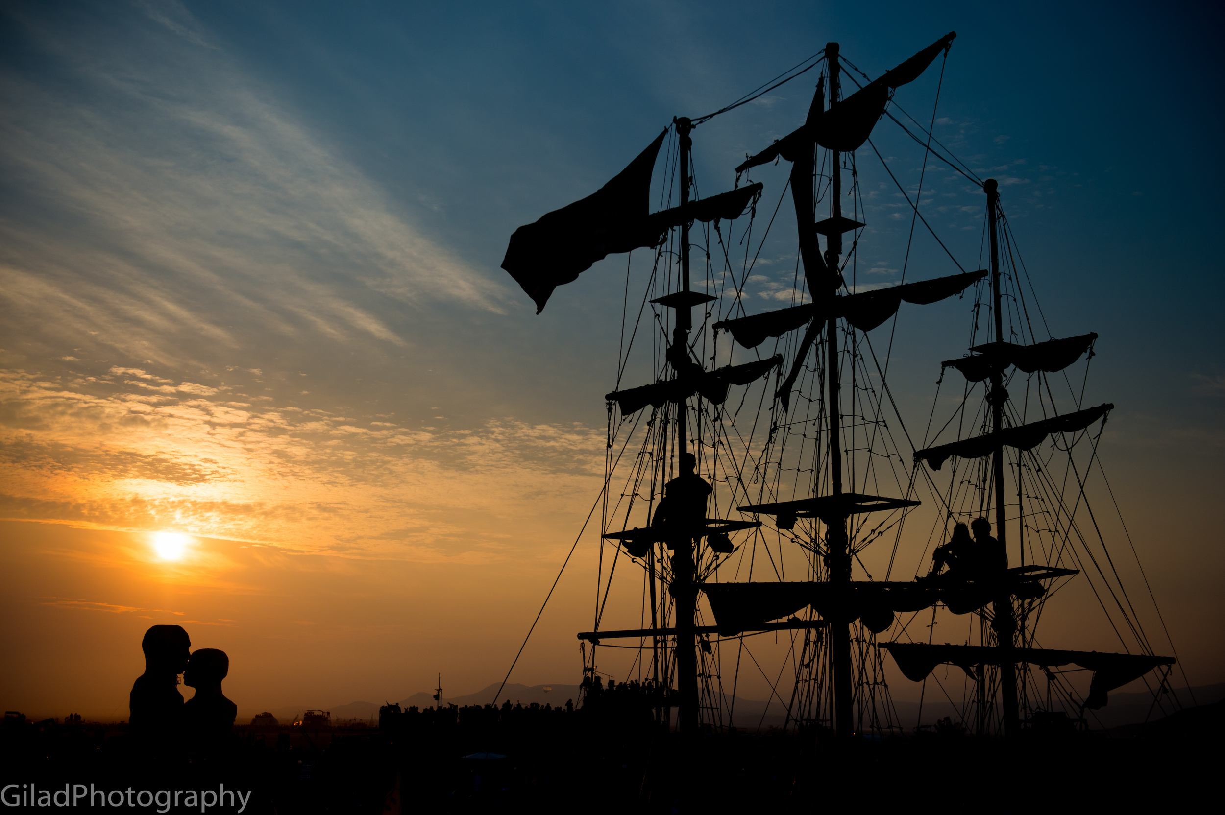 """A silhouette of a giant ship shaped art car with """"The Embrace"""" in the background at Burning Man 2014"""