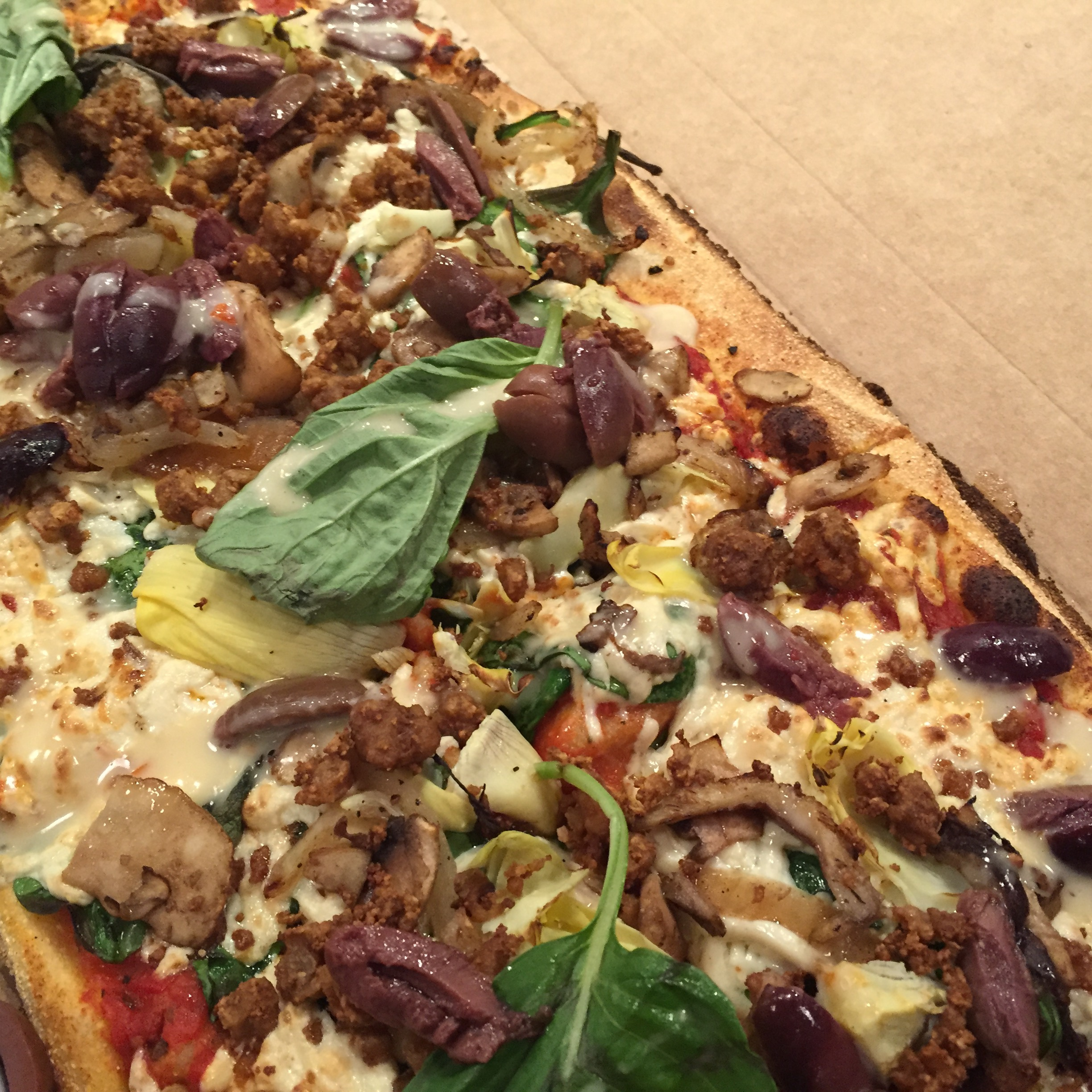 Pizza from &Pizza in DC-Toppings: mushrooms, olives, vegan crumble, vegan cheese, artichoke hearts, basil, garlic oil