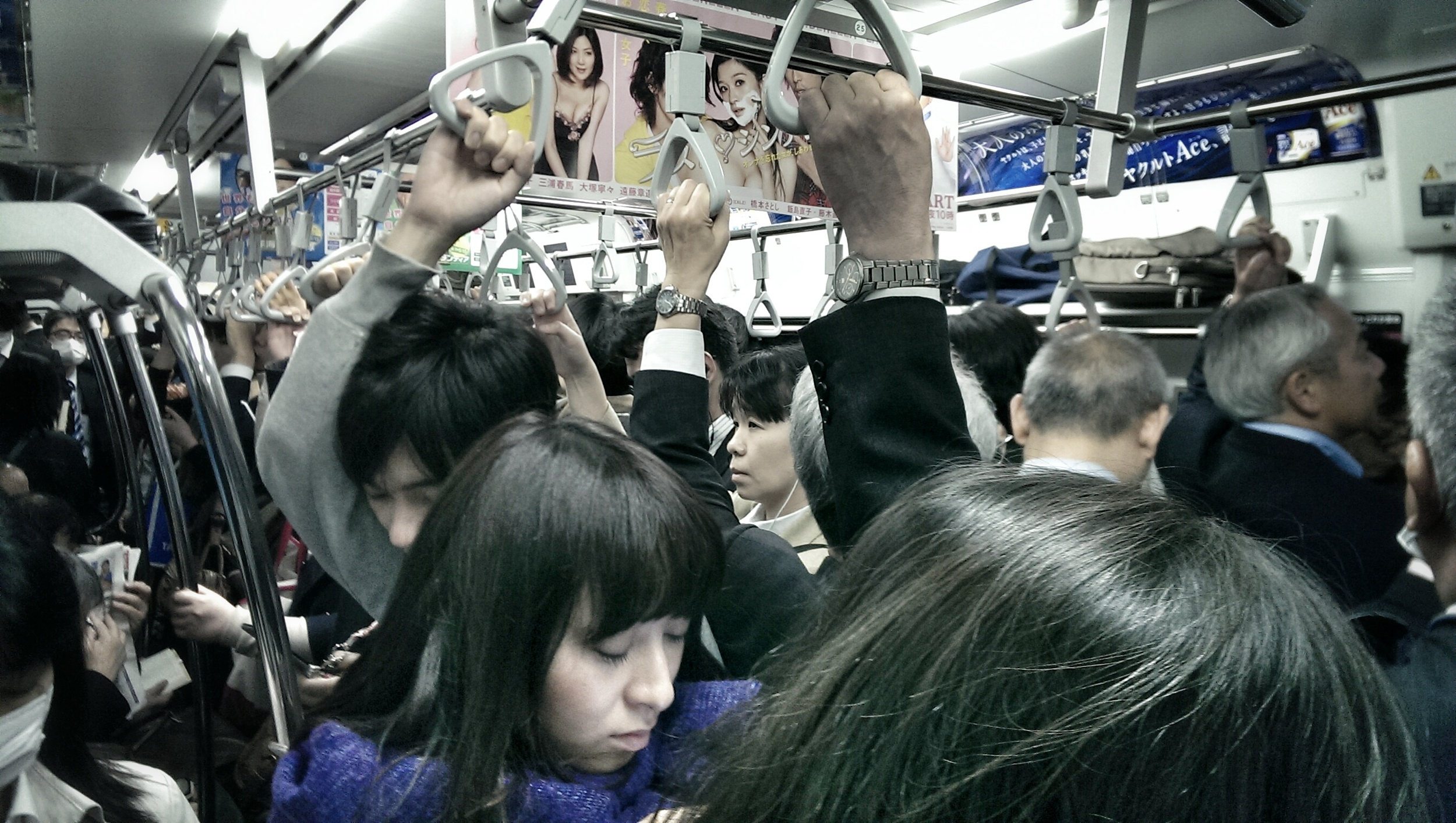 Tired faces during evening rush hour on the JR Yamanote Line.