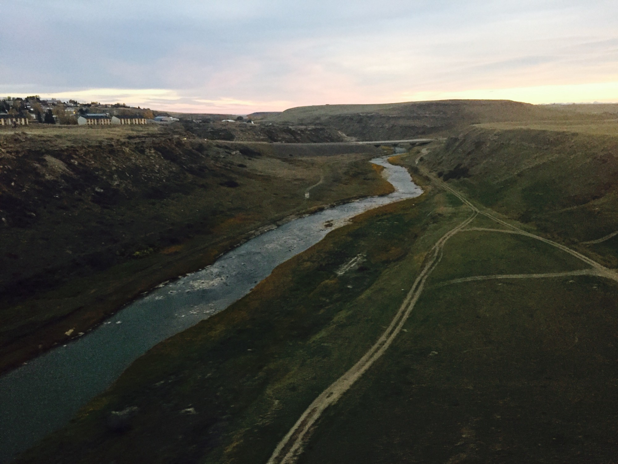 Desire lines along the creek leading to a road. The creek can also be considered a natural path, as the water has chosen the path of least resistance. Photo by Jessie Lacey taken from a train making its way through Cut Bank, Montana.