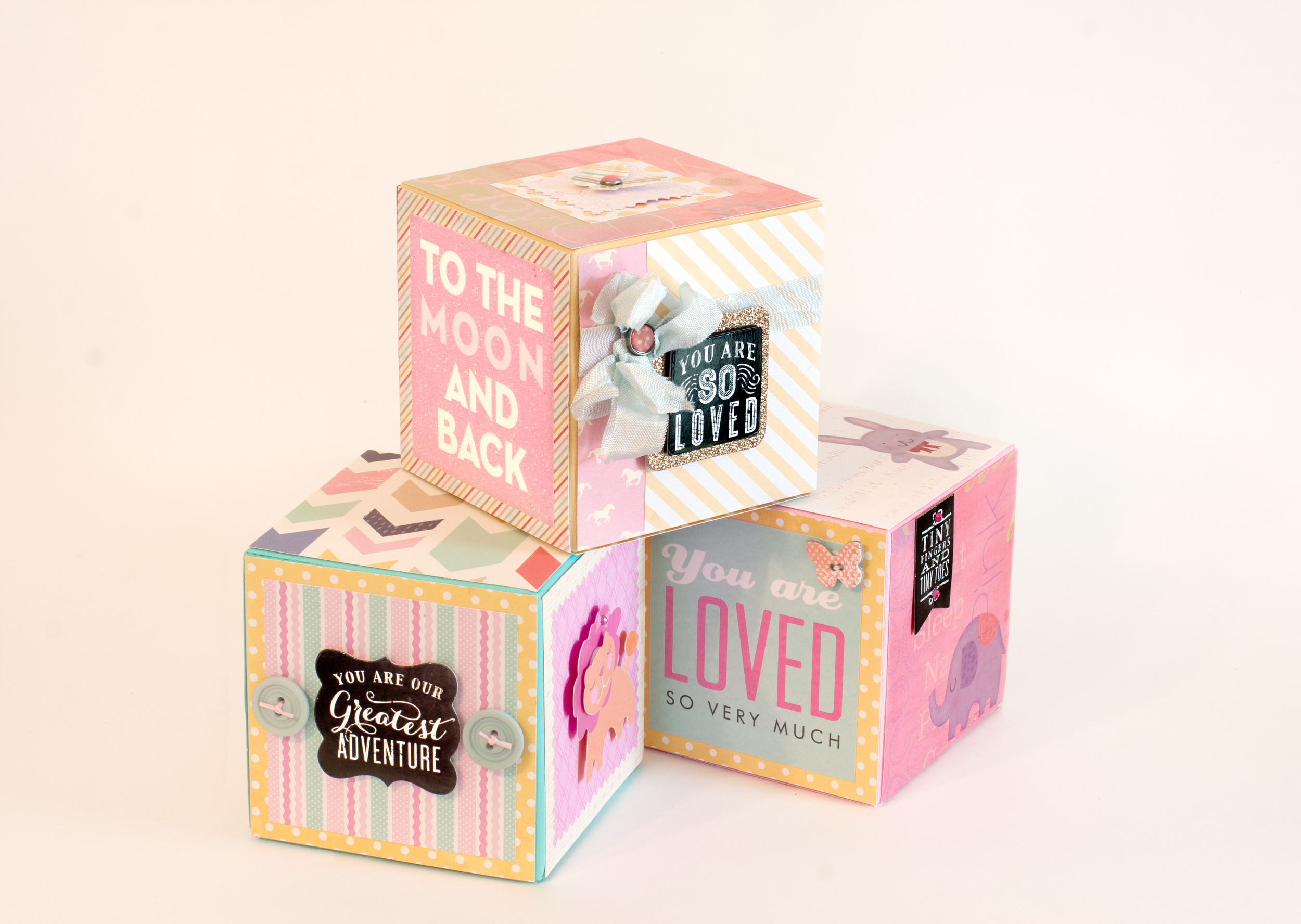 Baby Girl blocks decorated with mambi embellishments and papers.