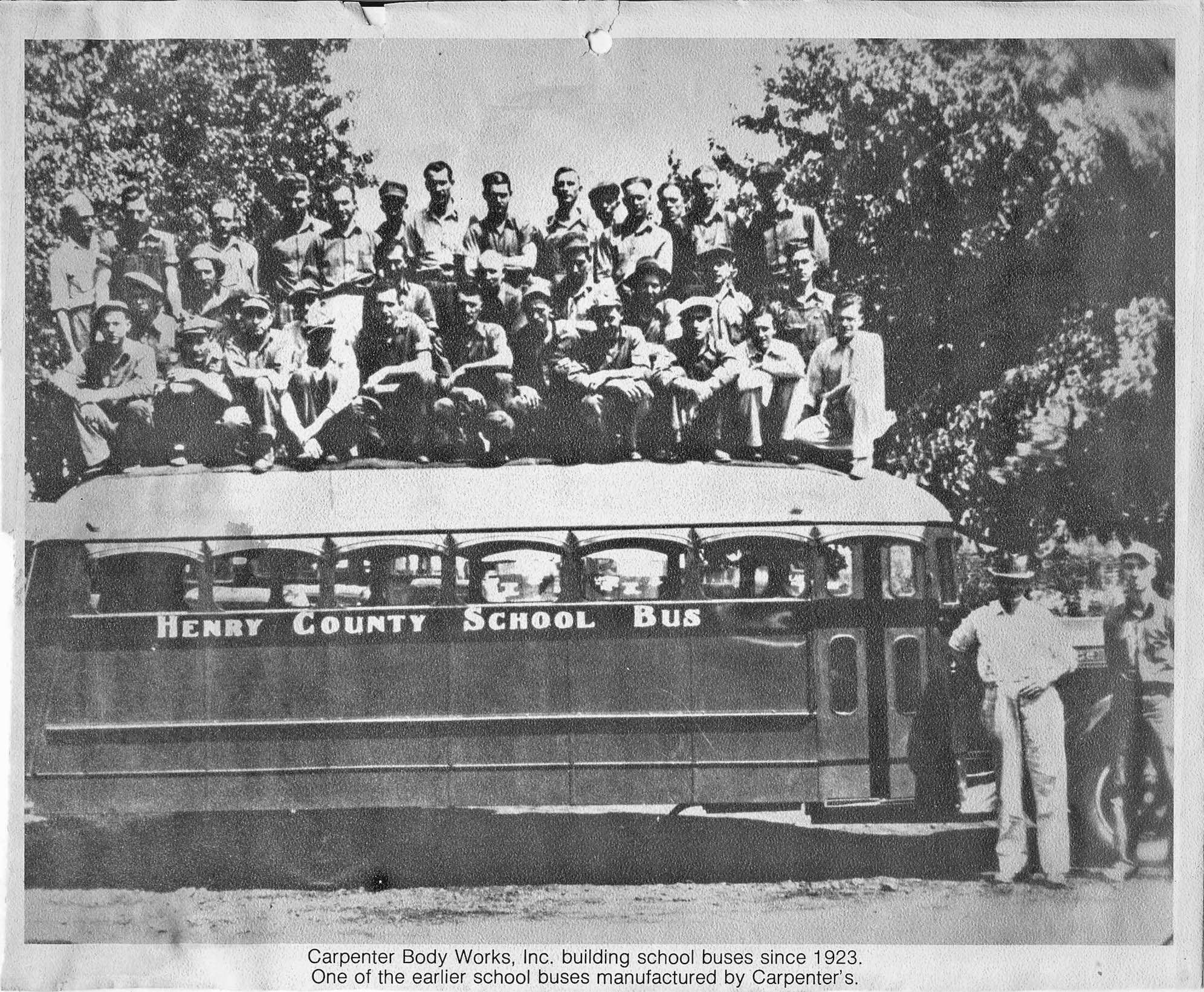 This is the first all-metal school bus ever produced by Carpenter Body Works. It is a 1935 Dodge bus. All 35 Carpenter employees are standing on top of the bus, and Ralph Carpenter and Ollie Eager standing in the foreground.