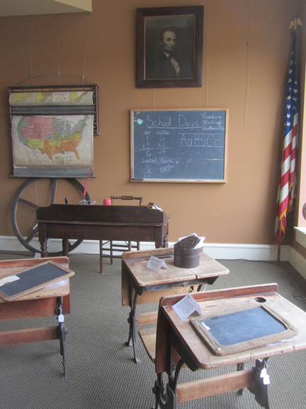 This museum gallery exhibit represents an early Lawrence County schoolroom. The wheel came from the bell tower at Central School. The maps were from the Springville School. At the beginning of the day, students recited the pledge of allegiance in front of an American flag such as the one shown in the corner.