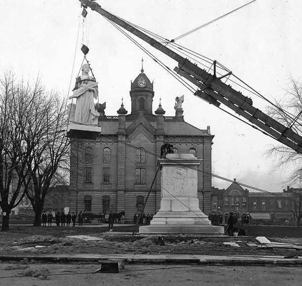 """Miss Indiana"" traveled by train from the Easton carving studio to J Street just west of the courthouse. A wooden derrick was built to move her from the train. She was hoisted to the top of Charles Morton Dodd's beautifully carved pedestal in November 1923."