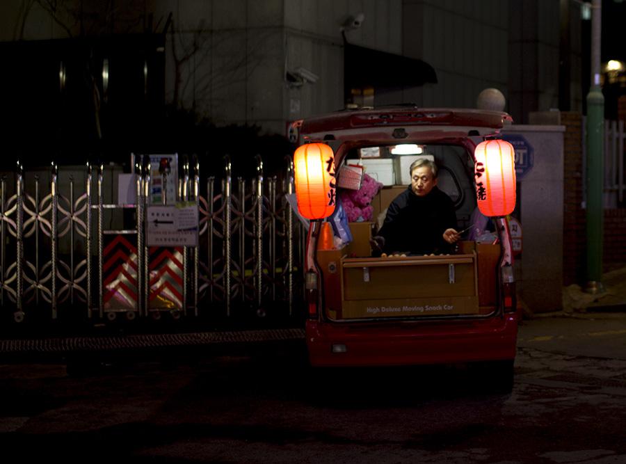 A street vendor making Japanese style takoyaki, fried octopus balls.