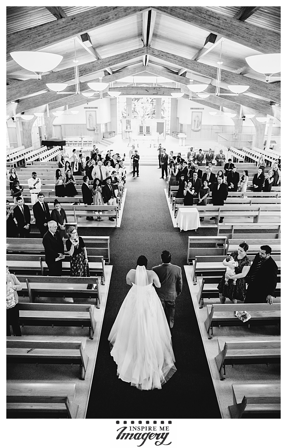 The bride makes her way down the aisle with her father.