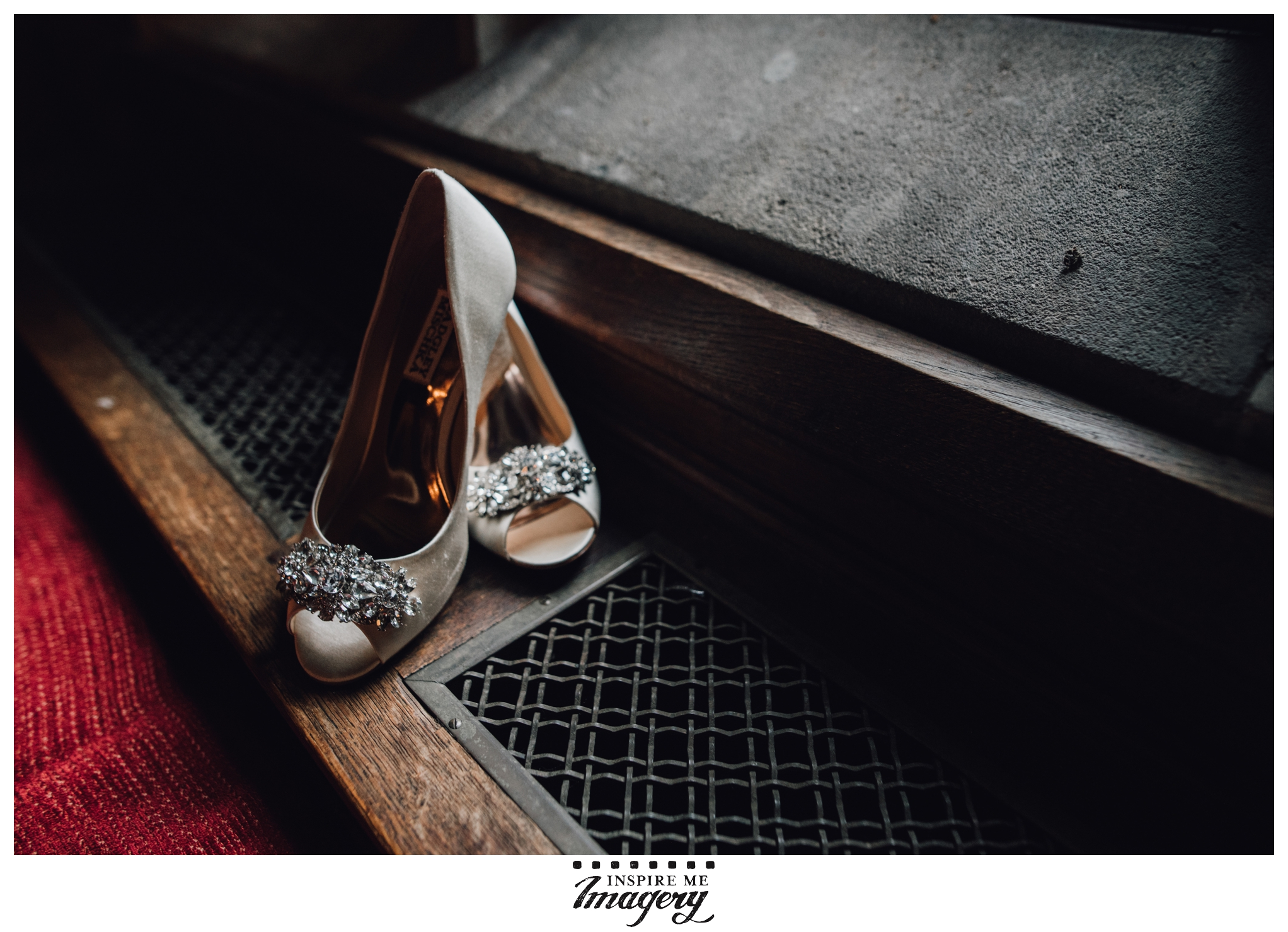 The bride's shoes sit in soft window light against the rich tones of the metalwork, the old wood, and the red carpeting.