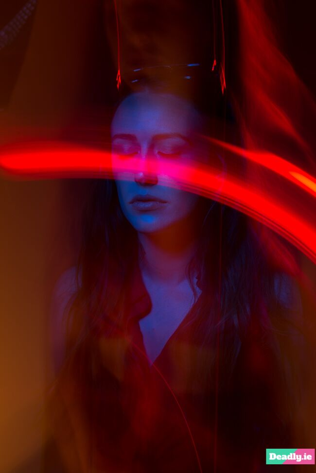 A colour gel portrait in which light has streaked across the models face due to pointing the camera at the light during the exposure.