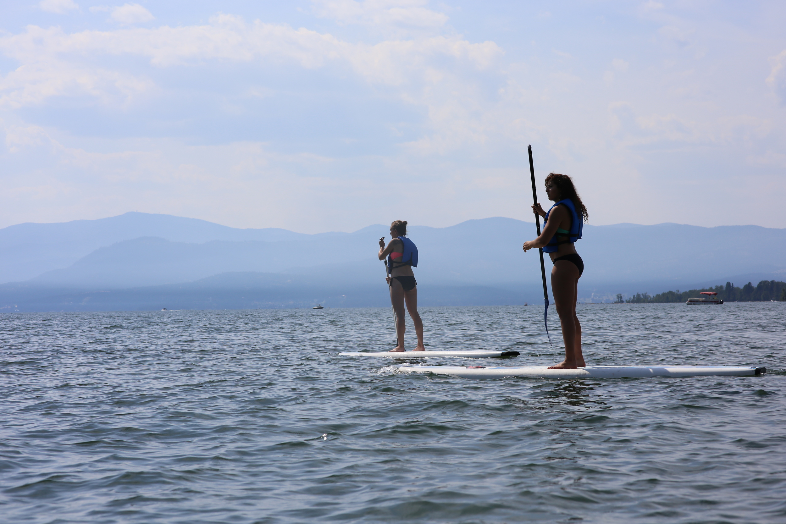 8/9/14  | Sarah Smith and Sarah Al-Khayyal take a break from railroading to paddle board  Flathead Lake in Whitefish, MT.  (Credit: Tyler Metcalfe, National Geographic Travel)