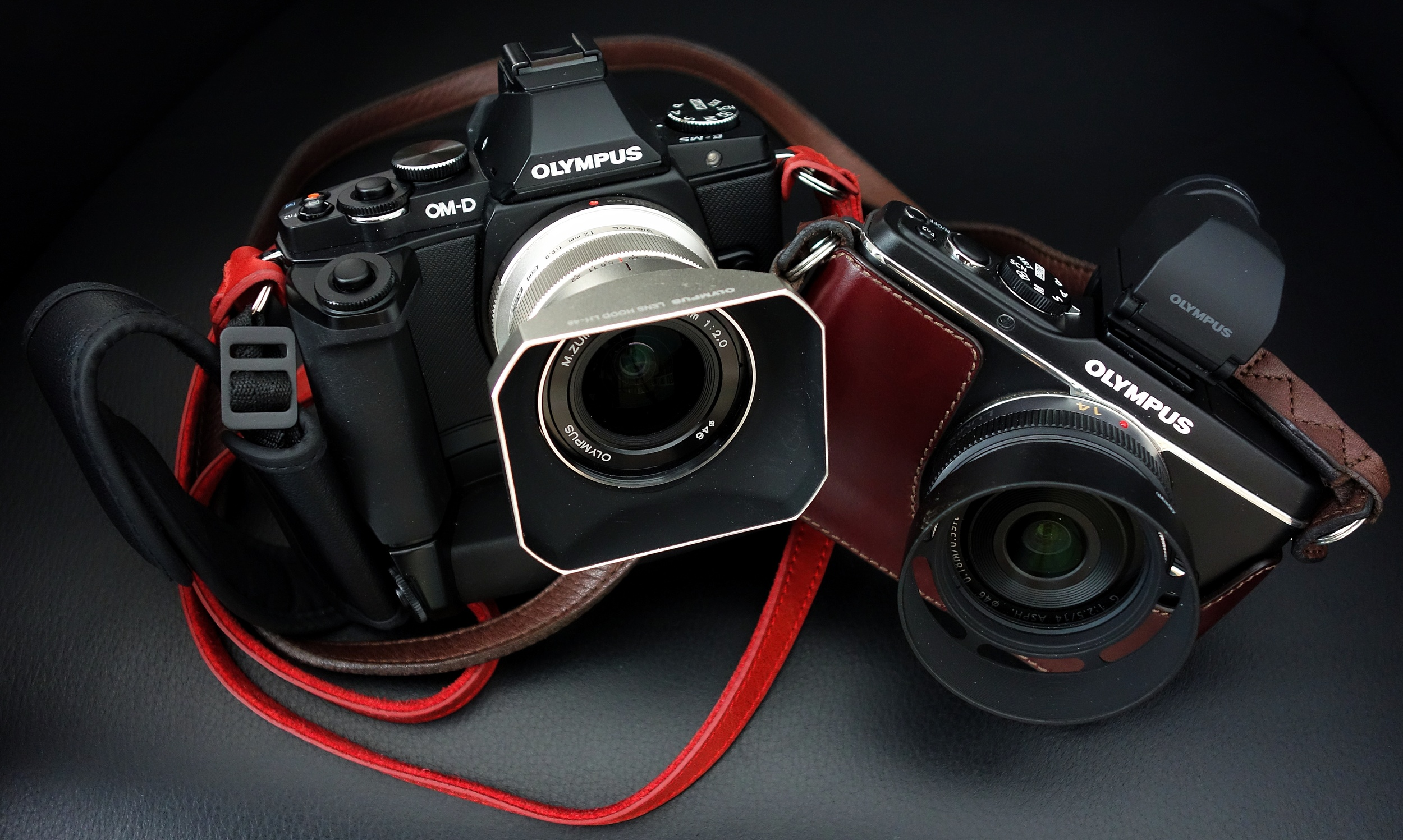 Sporting a magnesium alloy body, weather sealing, a 16MP sensor, 5-axis in-body image stabilisation, tilting touchscreen and electronic viewfinder, 2011's Micro Four-Thirds OM-D E-M5 was a mirror-less tribute to the legendary OM line of film cameras and 2012's Camera of the Year. Seen here with handgrip, battery holder, 12mm f2 lens and it's sister, the E-P3