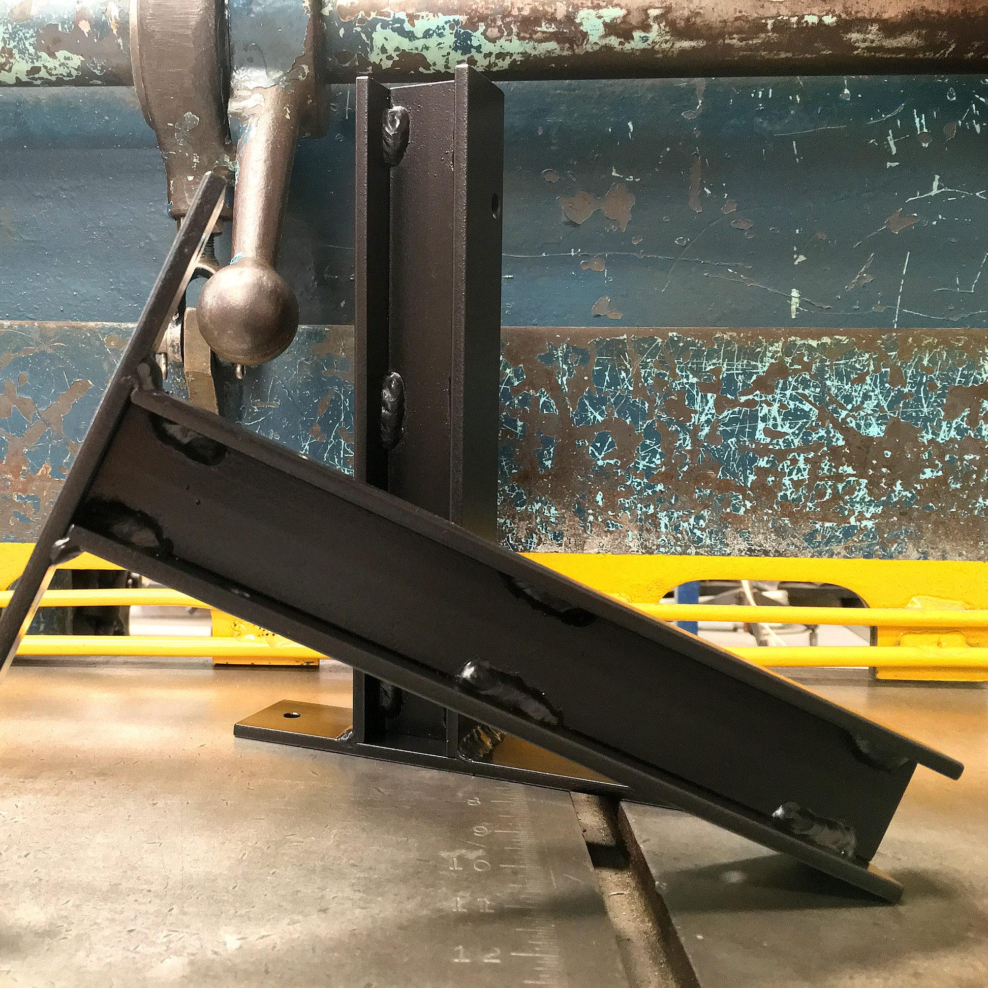 Black I-beam shelf bracket on vintage machinery.