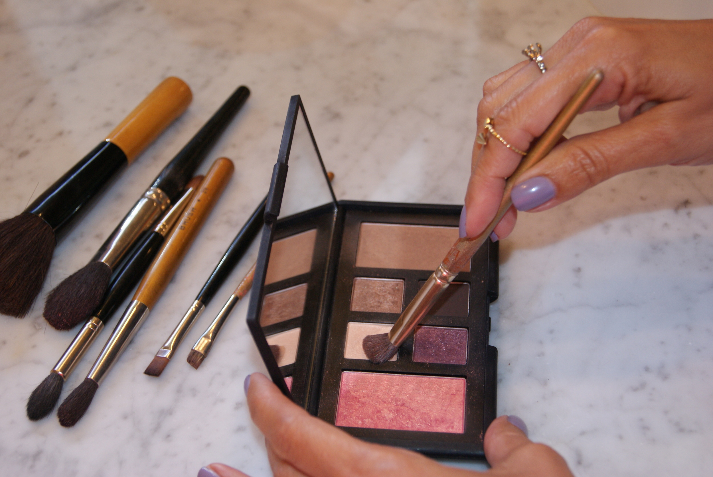 Step 2. Using a flat smaller brush, apply the sheer peach with gold pearl shade as a base and under the brow bone.