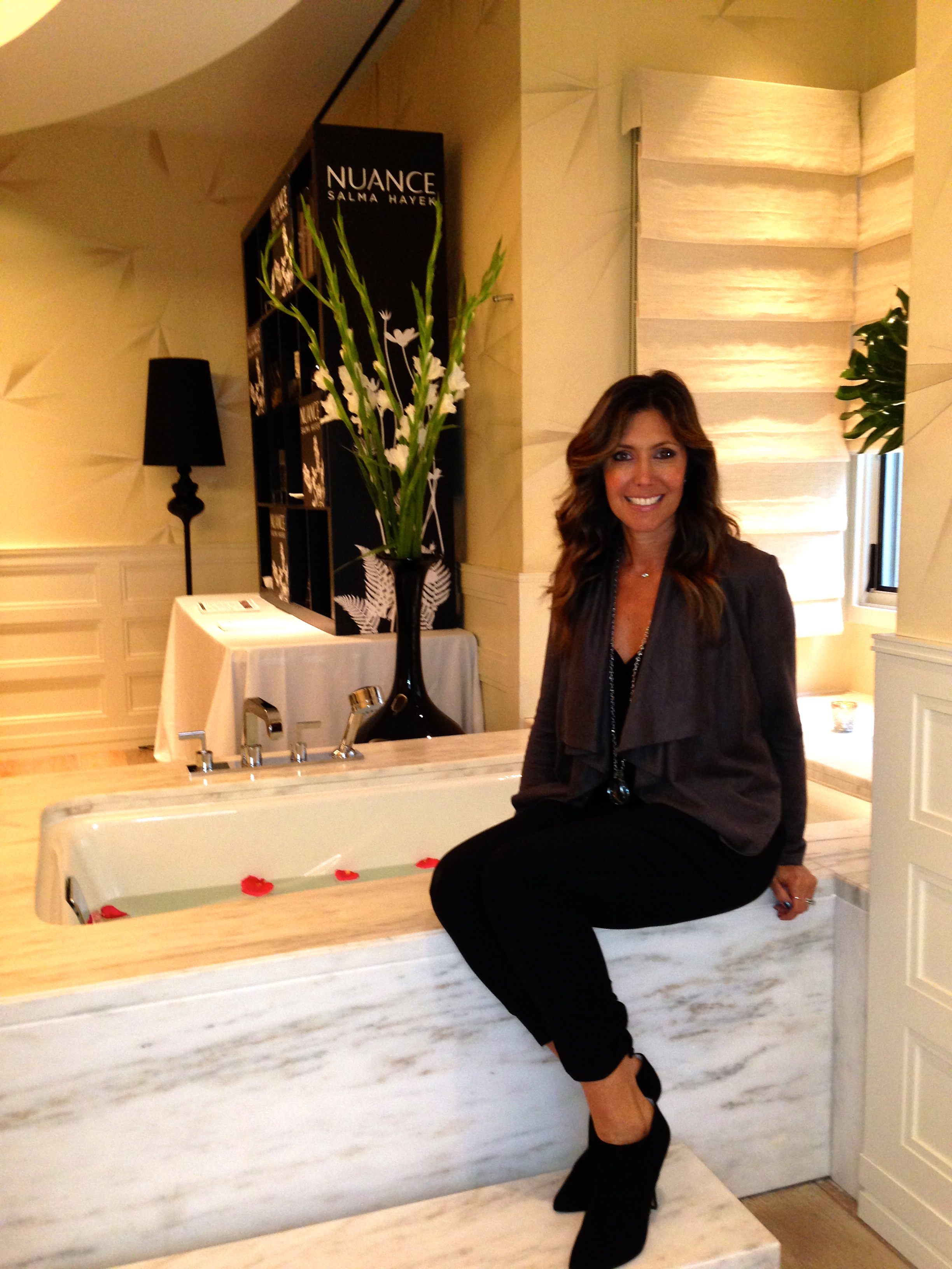 At Salma Hayek's Nuance for CVS beauty event at the Hotel Bel Air. Jumpsuit worn with suede grey jacket.