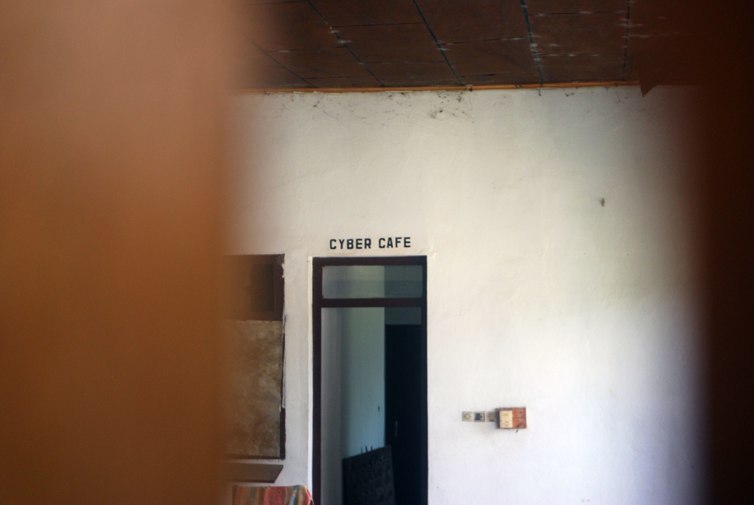 A picture of the Cyber Café entrance, taken through the slats of a boarded up window in the abandoned luxury hotel at Boali Falls.