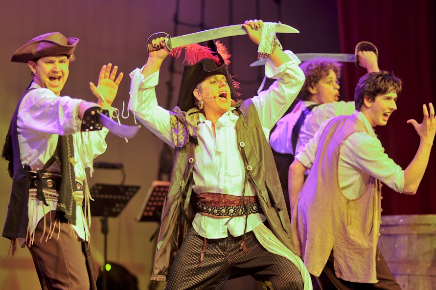 """PIRATES - High energy mischief fills the stage as these wayward pirates and their Pirate King present a medley of fabulous, well loved music from Gilbert and Sullivan's """"The Pirates of Penzance""""."""