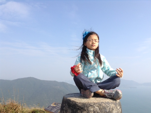 My daughter meditating during a  hike in Hong Kong