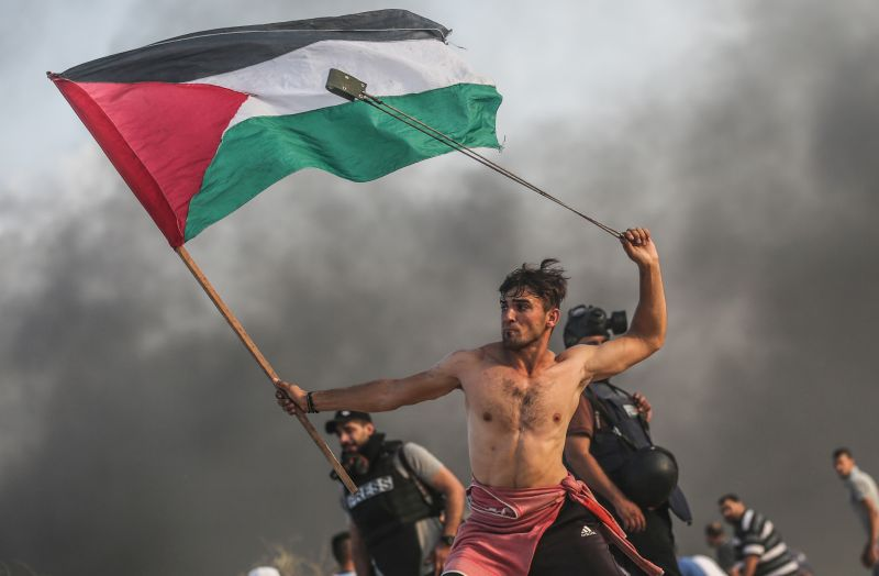 A shirtless young protester in Gaza gripping a Palestinian flag with one hand and swinging a slingshot over his head with the other, on the northern border between Gaza Strip and Israel in the weekly protests, which are organized by Palestinian protesters to protest against the Israeli blockade of Gaza which is imposed by Israel for 12 years until now.   Photograph by  Mustafa Hassona