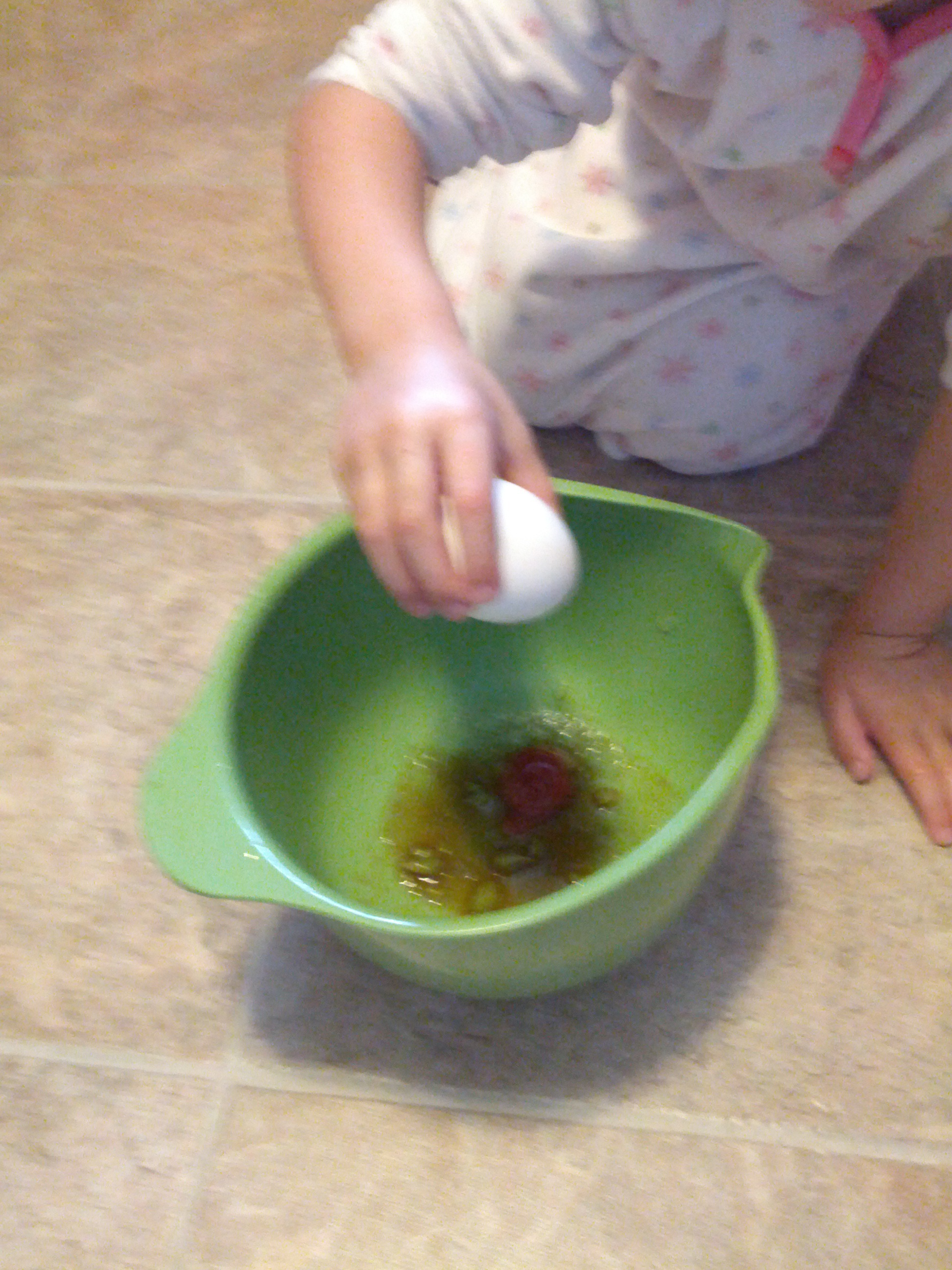 Adding an egg to the other wet ingredients.