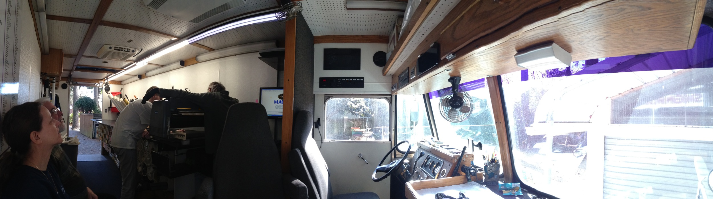 panorama of the whole van. the people on the left are sitting in little jump seats attached to the wall just inside the door. The 'reception area' for clients, if you will.