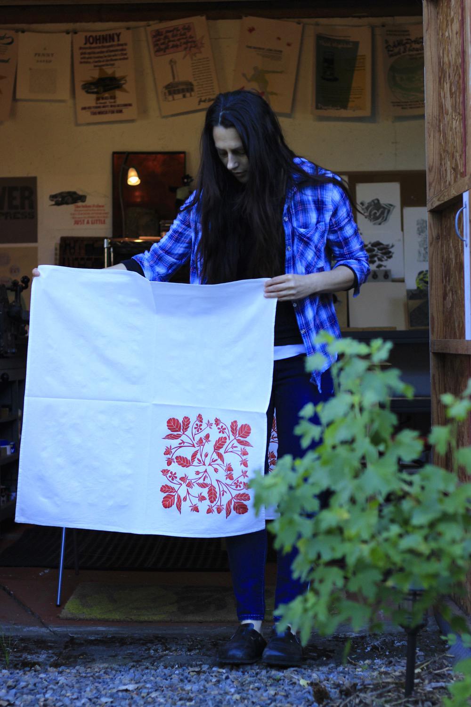In front of my studio, holding a linocut print tea towel