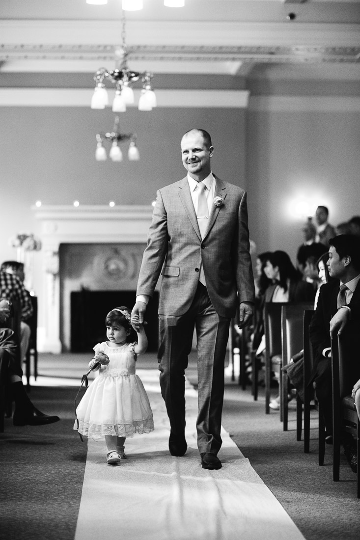 groomsman and daughter walking down the aisle at the vancouver club wedding ceremony