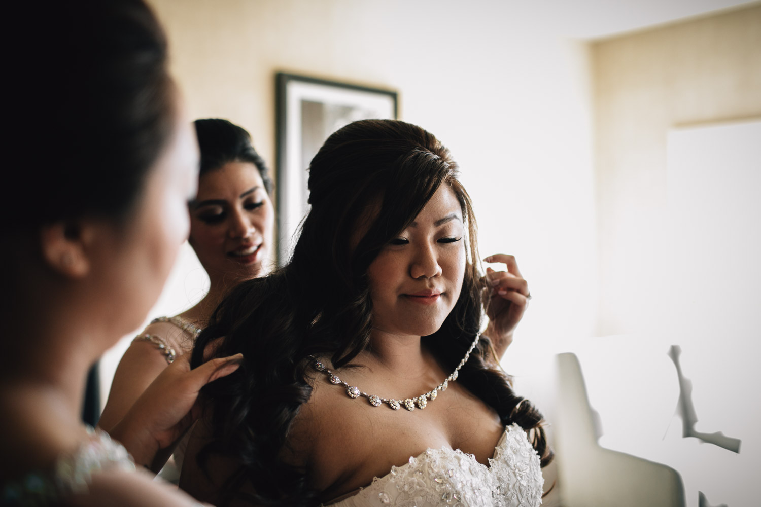 bride putting on jewllery for wedding in surrey photography