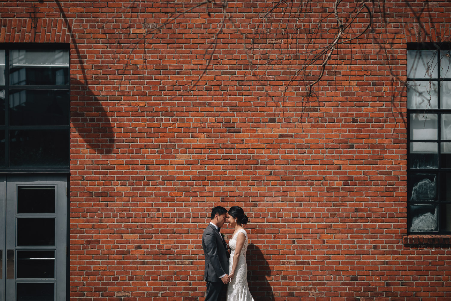 wedding portraits of bride and groom against brick wall in yaletown roundhouse vancouver bc