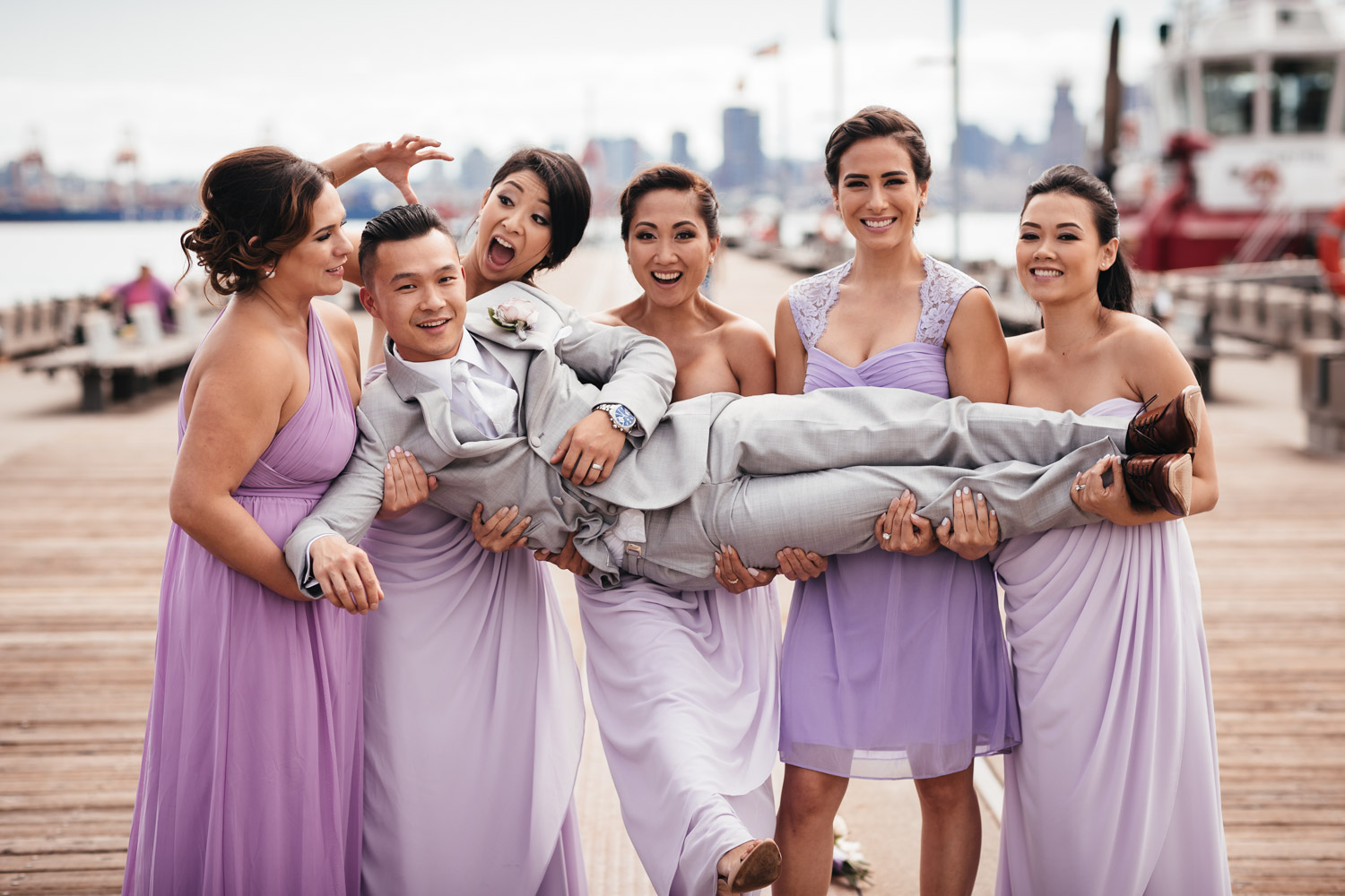 groom with bridesmaids in north vancouver for wedding at burrard dry dock pier