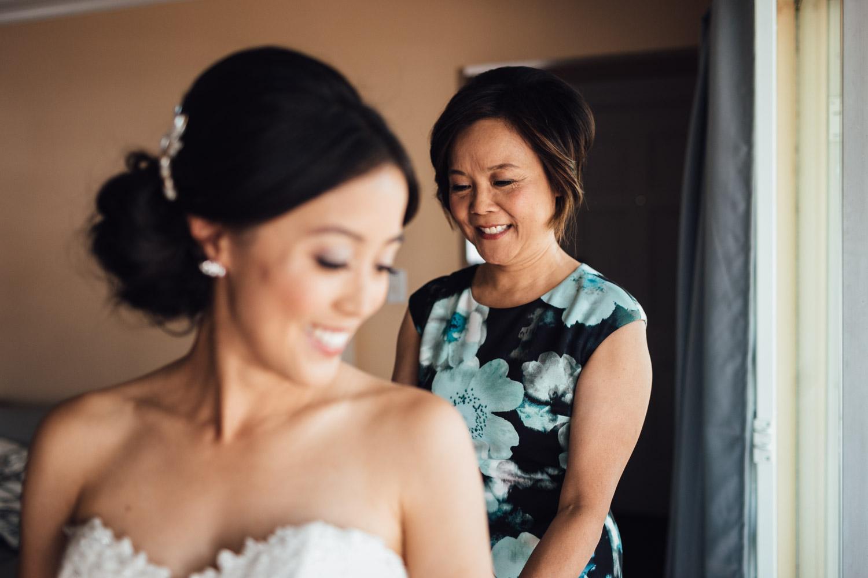 east vancouver wedding photography mother doing up wedding dress