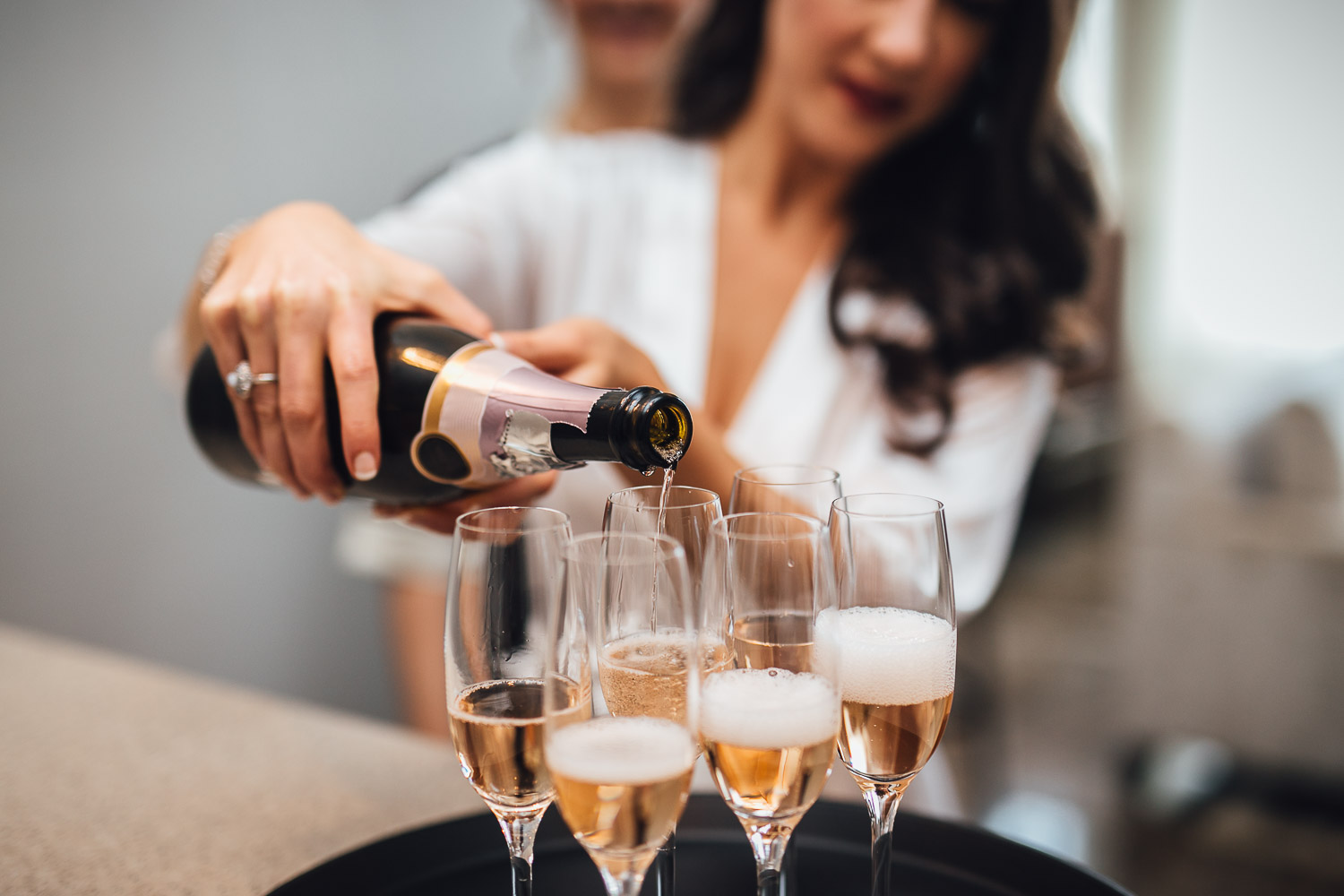 bride pouring champagne getting ready at delta hotel burnaby wedding photography