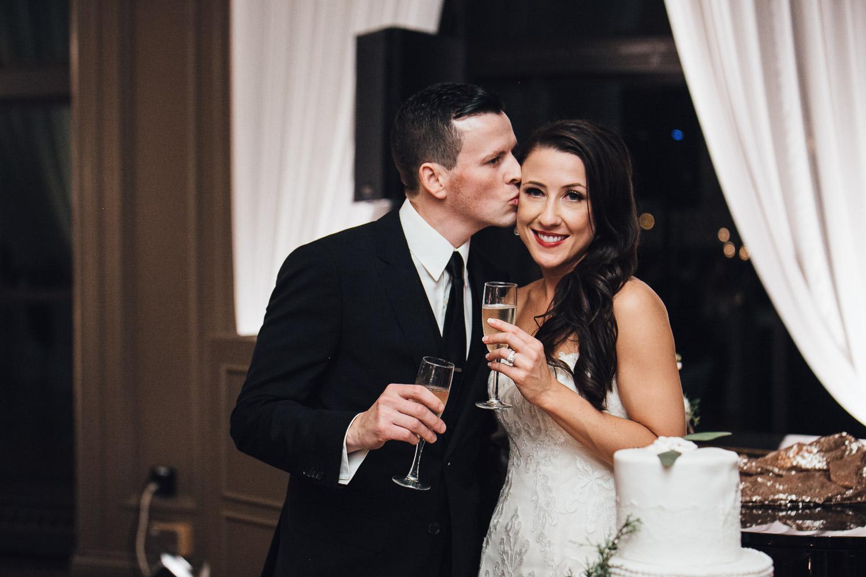 groom kiss bride cake cutting swaneset wedding reception photographer