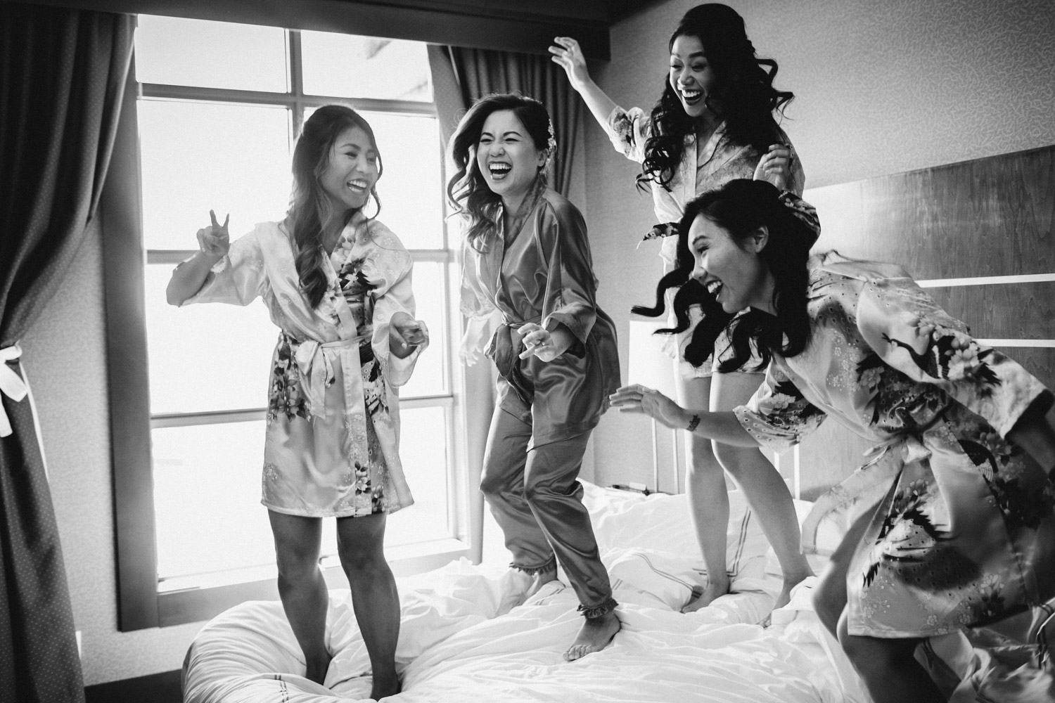 bride and bridesmaids jumping on bed candid river rock casino hotel wedding photography