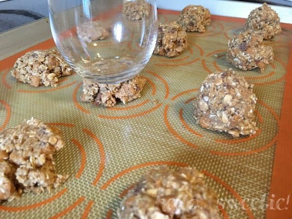 Flattening the tops of dense cookies with a glass will help them to bake more evenly.