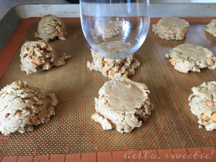 Flattening the domes slightly will help the cookies bake through evenly.