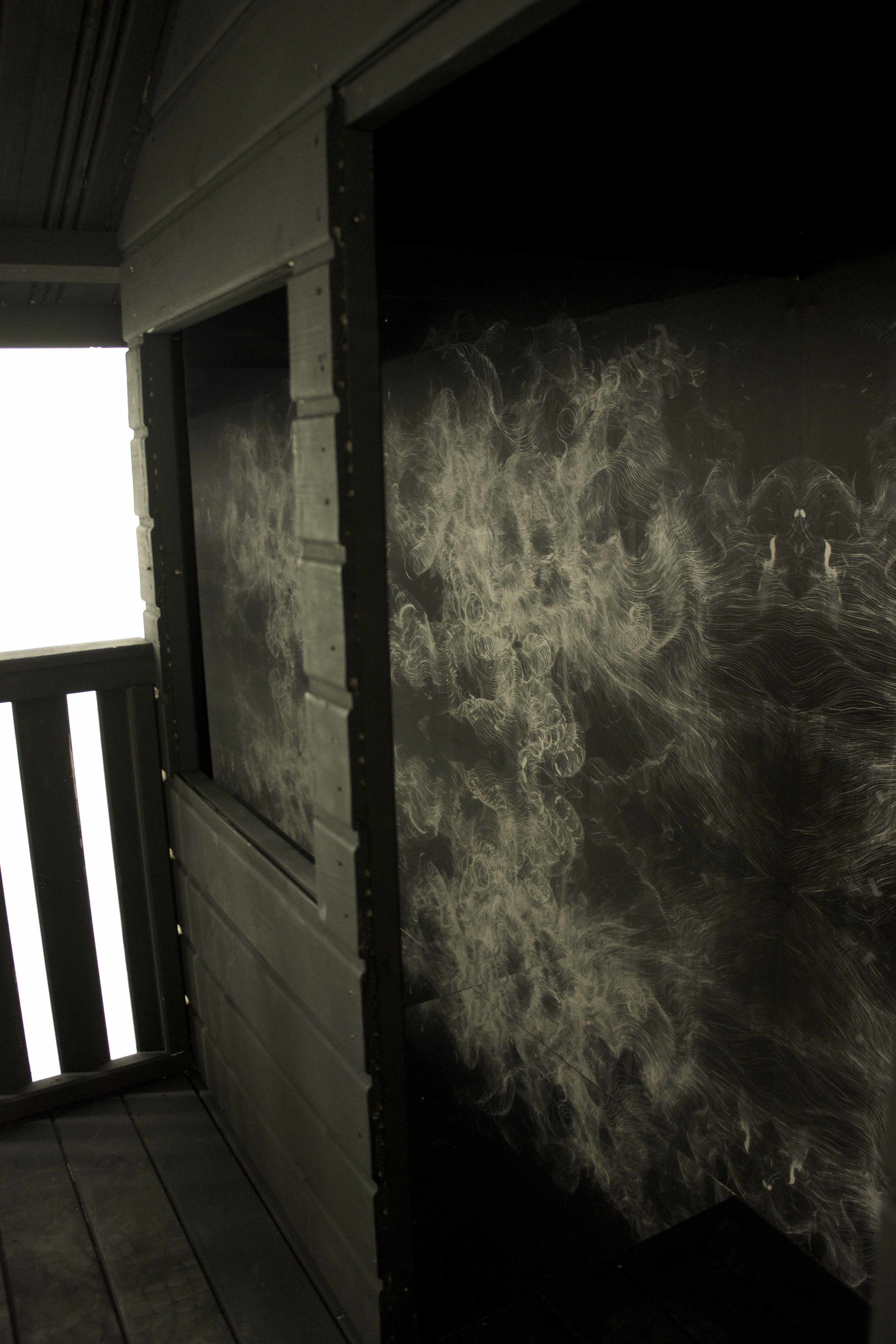 Interior shot through door of 'Infinity shed', white ink mural and mirror