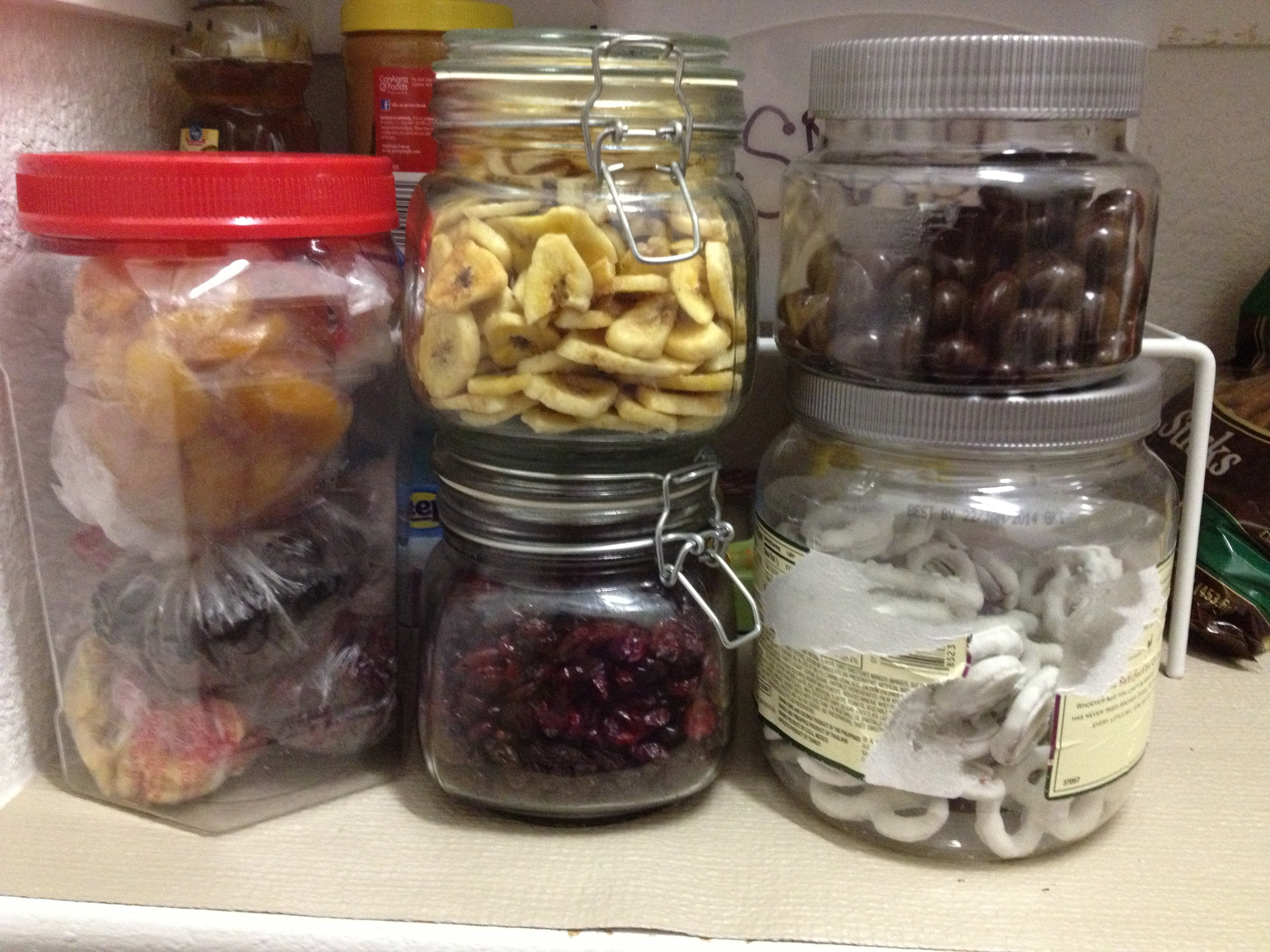 Hinged canisters from Dollar Tree. Upcycled Market Pantry trail mix containers for pretzels and dark chocolate - still need to remove the label on the big one. HUGE Jelly Belly container for some other dried yummies -- and yes, I will probably spray paint that lid too!