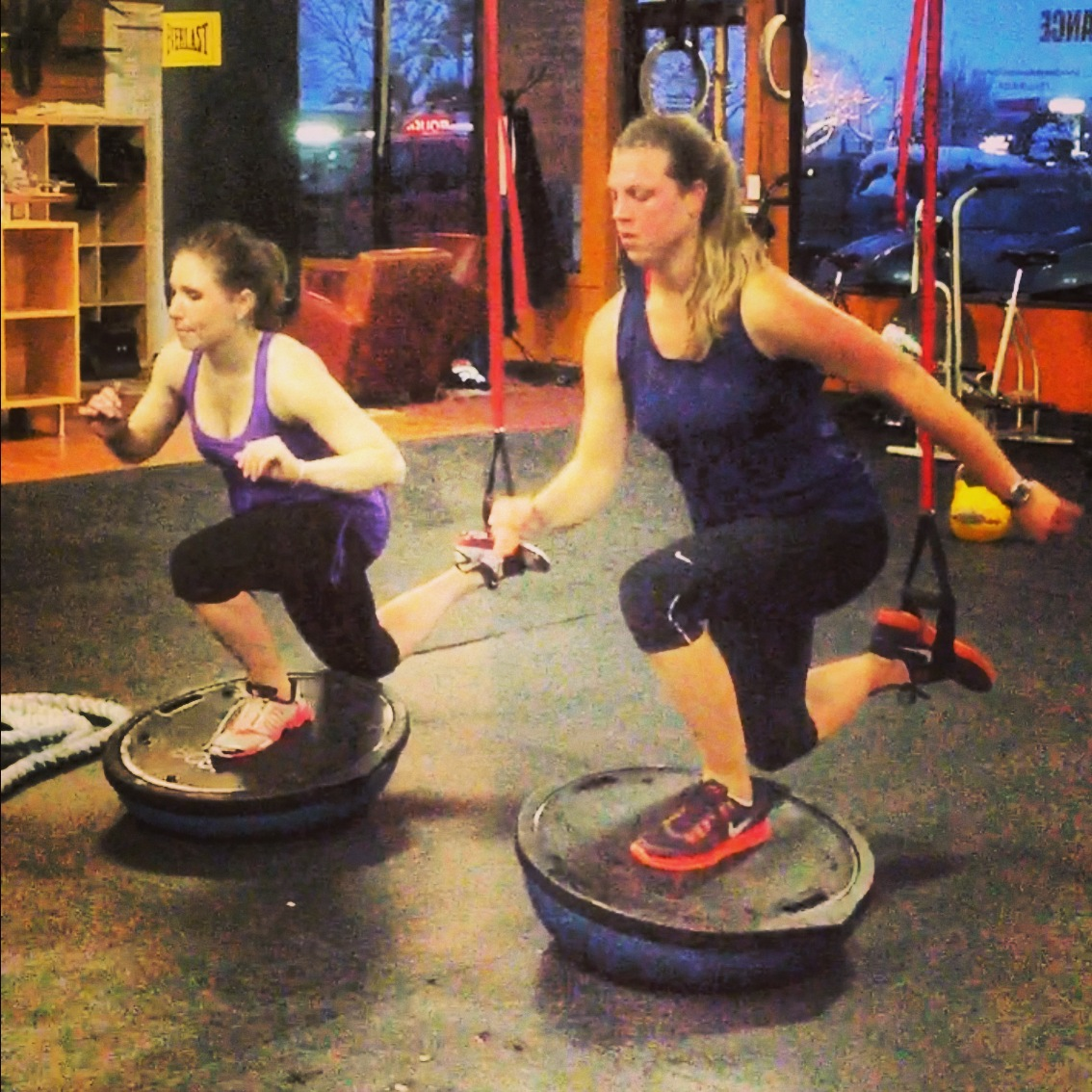 Courtney and Kristin perform single leg squats on a BOSU ball. One of the more challenging group session exercises
