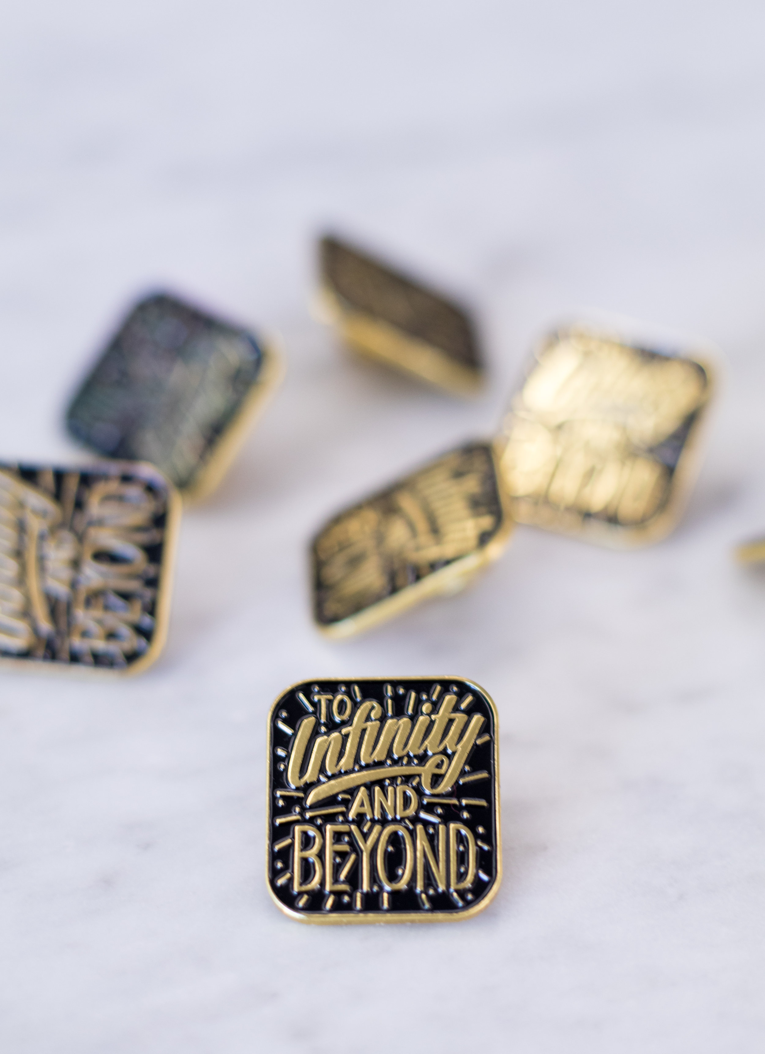 Enamel pins with custom hand-lettering.