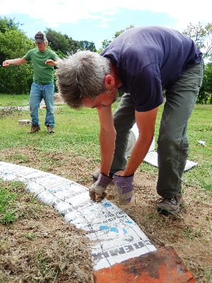 Skylar Aaseby and Seth Davis arrange earth-bags to serve as a retaining wall for terraced garden bed. The earth bag wall will also enclose pipes to move grey water from inside the house to irrigate the ground without flooding it.
