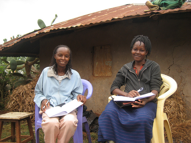 "Ann Ndwiga, in her home village, studies the ""Where There is No Doctor"" textbook with a friend. Beneath that textbook sits her bible."